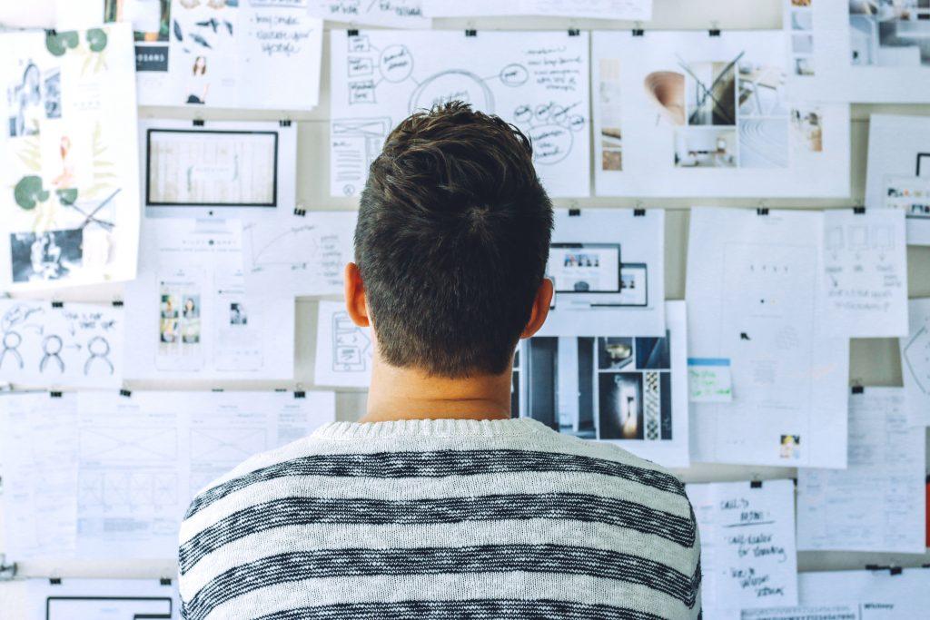 Designer steht vor Whiteboard und schafft messbaren Erfolg durch Design